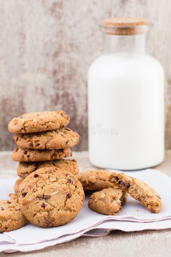 Biscotti del chip della farina d'avena del cioccolato con latte sui tum di legno rustici immagini stock libere da diritti
