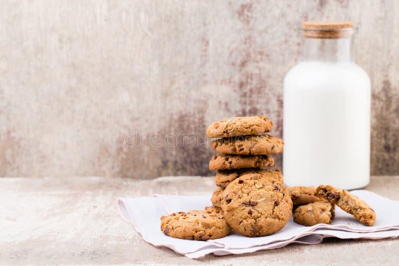 Biscotti del chip della farina d'avena del cioccolato con latte sui tum di legno rustici immagine stock