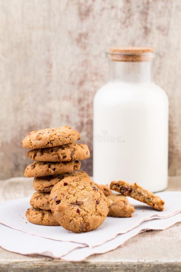 Biscotti del chip della farina d'avena del cioccolato con latte sui tum di legno rustici fotografia stock libera da diritti
