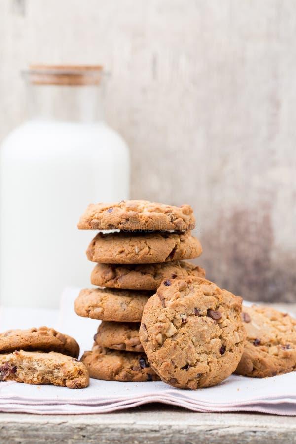 Biscotti del chip della farina d'avena del cioccolato con latte sulla tavola di legno rustica immagini stock