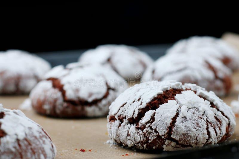 Biscotti del cioccolato con le crepe su carta bollente e iolated sul nero Biscotti incrinati del cioccolato immagine stock libera da diritti