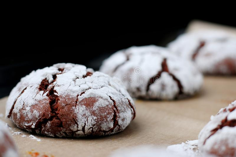Biscotti del cioccolato con le crepe su carta bollente e iolated sul nero Biscotti incrinati del cioccolato fotografia stock libera da diritti