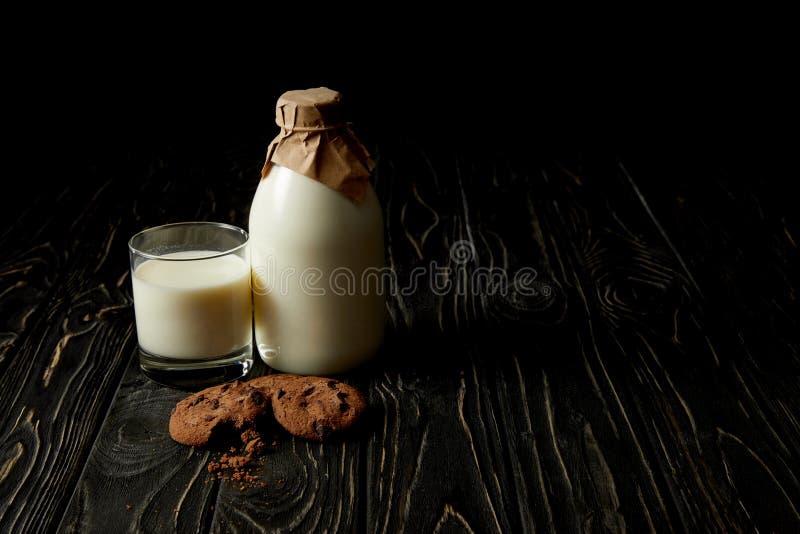 biscotti del cioccolato, latte fresco in vetro e bottiglia avvolta da carta su fondo nero fotografie stock libere da diritti