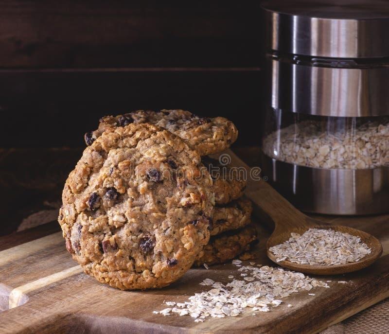 Biscotti del dado dell'uva passa della farina d'avena su un bordo di legno fotografia stock libera da diritti