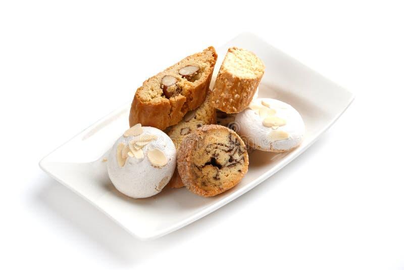 Biscotti del dado e della meringa in un piatto bianco su un fondo bianco isolato immagine stock