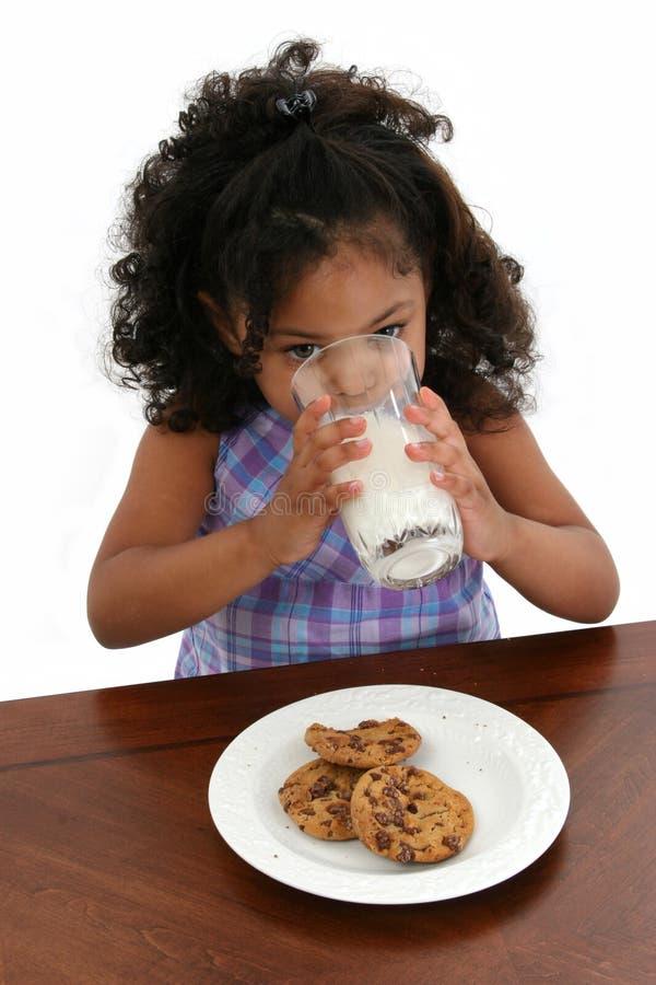 Biscotti del latte della ragazza del bambino fotografia stock libera da diritti