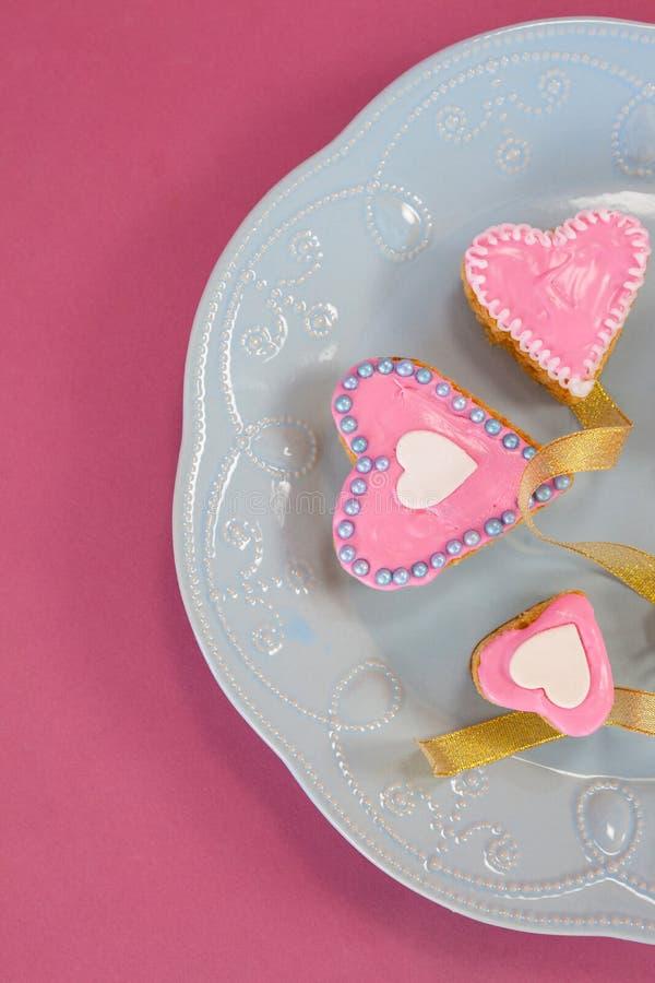 Biscotti del pan di zenzero di forma del cuore sul piatto fotografie stock