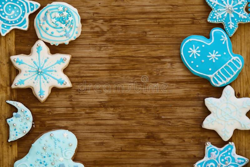 Biscotti del pan di zenzero di Natale con la decorazione blu su fondo di legno fotografie stock
