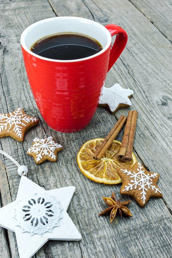 Biscotti del pan di zenzero di Natale con la tazza da caffè sul BAC di legno grigio fotografia stock