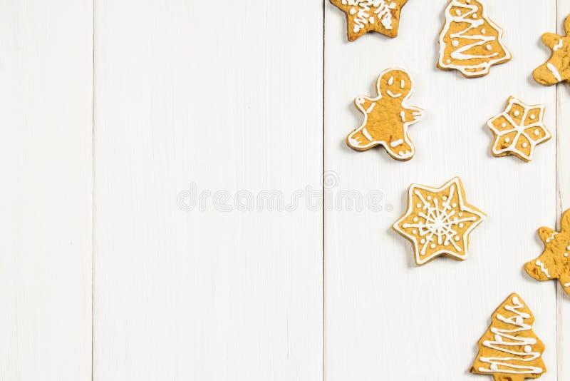 Biscotti del pan di zenzero di Natale delle forme differenti su una tavola di legno bianca Copi lo spazio fotografia stock