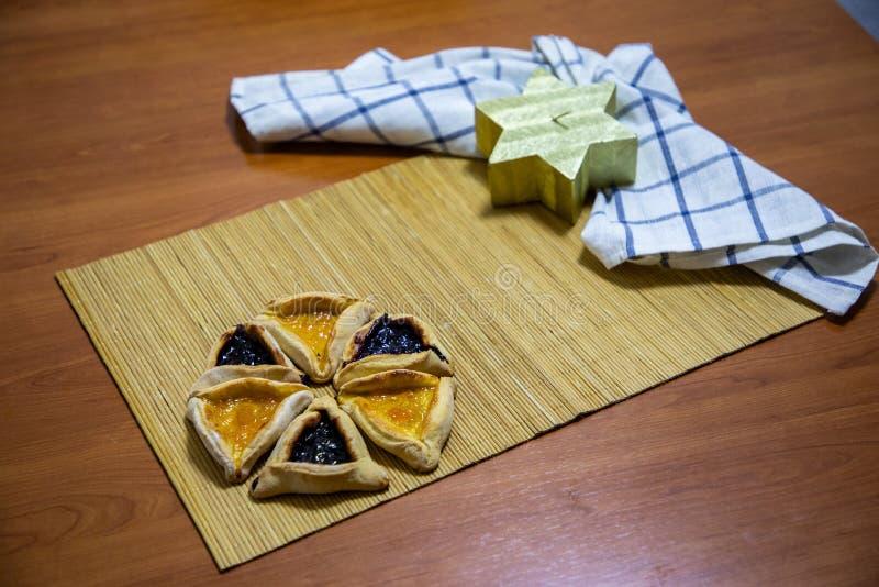 Biscotti dell'inceppamento del mirtillo e dell'albicocca di Hamantash Purim con la candela di legno di forma del fondo della tavo fotografie stock