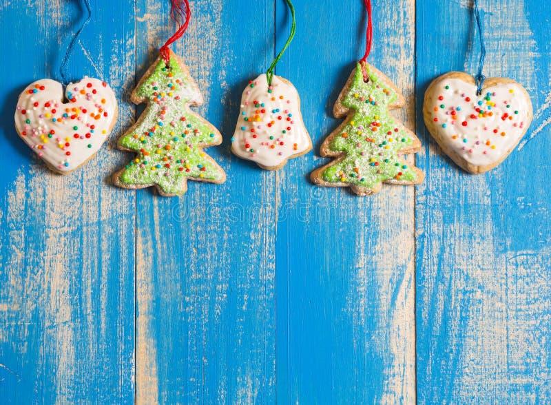 Biscotti dello zenzero di Natale con glassa su un fondo blu immagine stock