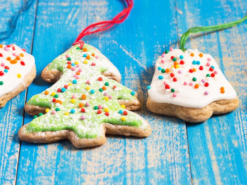 Biscotti dello zenzero di Natale con glassa su un fondo blu fine immagini stock