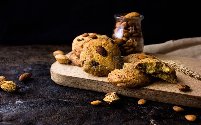 Biscotti di biscotto al burro americani con le gocce di cioccolato e una brocca di latte e di mandorle Fondo scuro di lerciume Lu fotografia stock libera da diritti