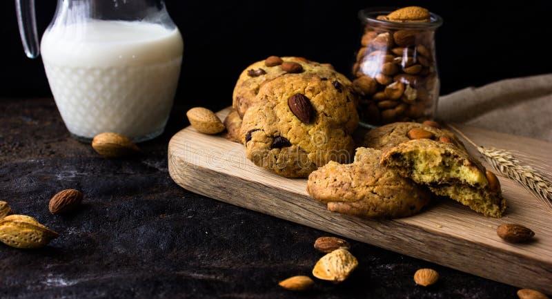 Biscotti di biscotto al burro americani con le gocce di cioccolato e una brocca di latte e di mandorle Fondo scuro di lerciume Lu immagini stock
