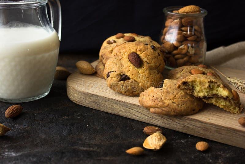 Biscotti di biscotto al burro americani con le gocce di cioccolato e una brocca di latte e di mandorle Fondo scuro di lerciume Lu fotografie stock
