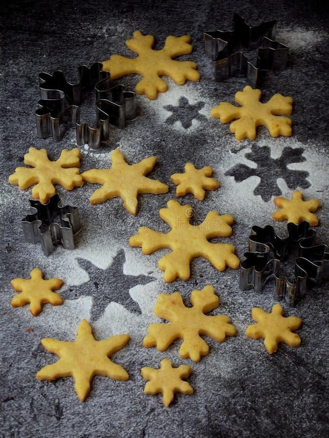 Biscotti di biscotto al burro di Natale sotto forma di fiocchi di neve che spruzzano le taglierine del biscotto e dello zucchero  immagini stock