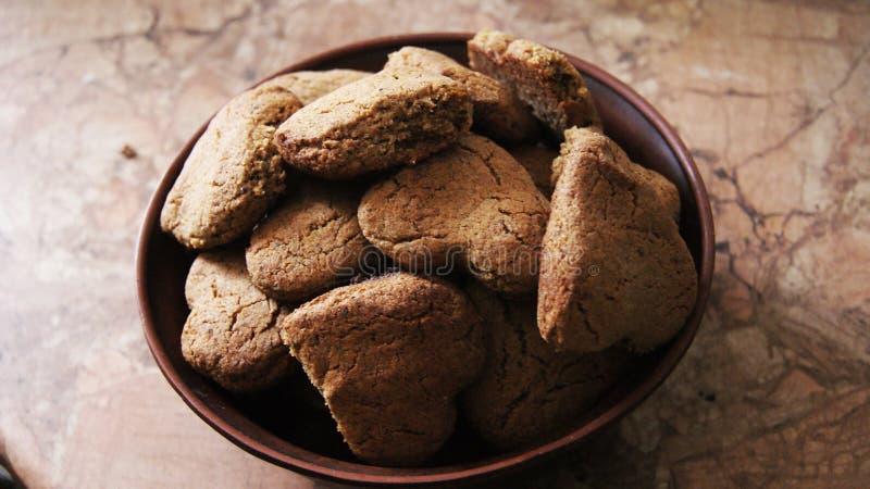 Biscotti di biscotto al burro sotto forma di cuori in una ciotola dell'argilla fotografia stock libera da diritti