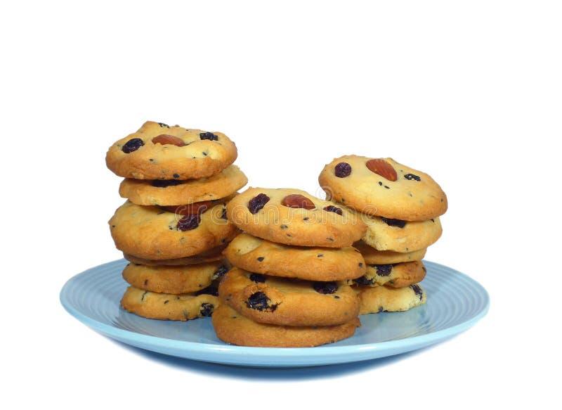 Biscotti di burro dell'uva passa della mandorla accatastati su su un piatto isolato su fondo bianco fotografie stock libere da diritti