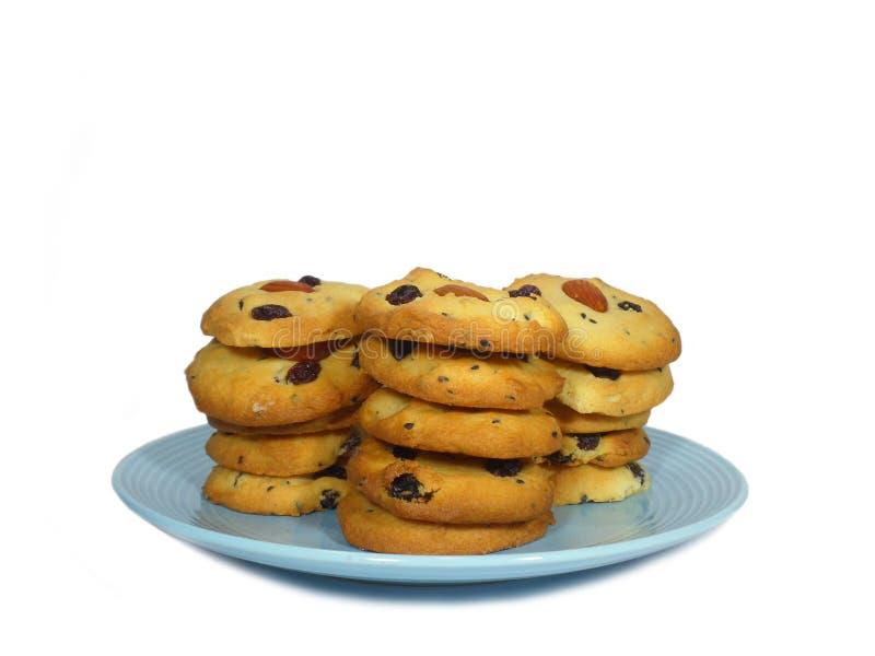 Biscotti di burro su accatastati dell'uva passa della mandorla su un piatto blu isolato su bianco fotografia stock