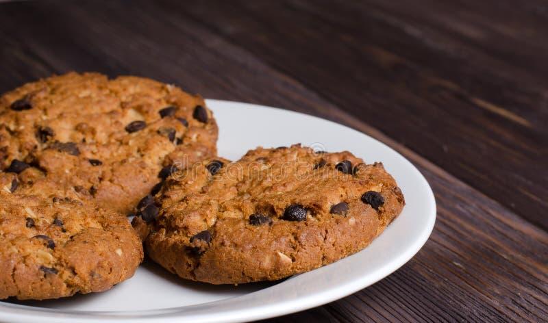 Biscotti di farina d'avena casalinghi su un piatto bianco Priorit? bassa di legno fotografia stock