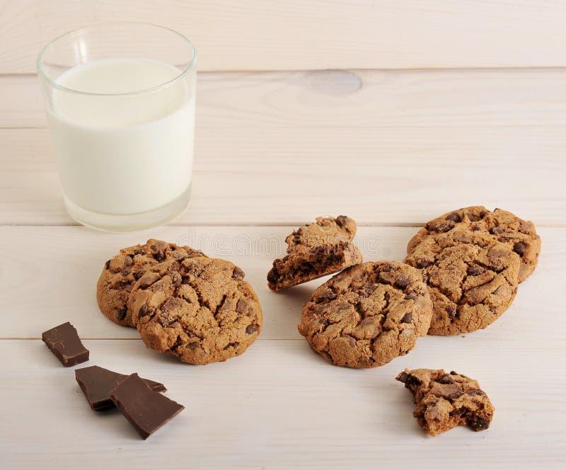 Biscotti di farina d'avena con cioccolato e un bicchiere di latte sul BAC di legno fotografie stock