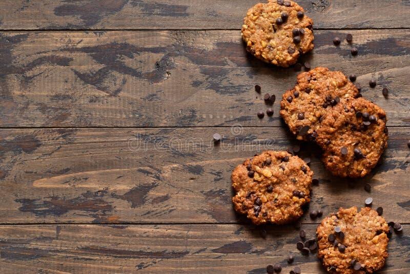 Biscotti di farina d'avena con le gocce di cioccolato su un fondo di legno fotografie stock libere da diritti