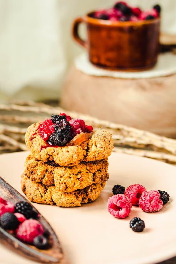 Biscotti di farina d'avena croccanti del vegano casalingo con l'inceppamento di lampone ed il caramello della data su un fondo di immagine stock