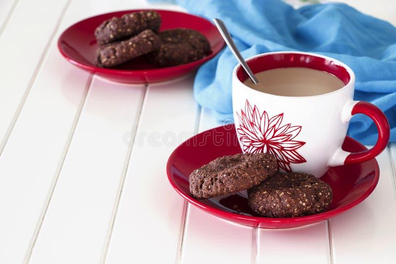 Biscotti di farina d'avena del cioccolato e tazza del tè del latte Fondo di legno blu e bianco fotografie stock