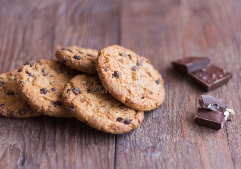 Biscotti di farina d'avena deliziosi e croccanti con cioccolato su fondo di legno immagine stock libera da diritti