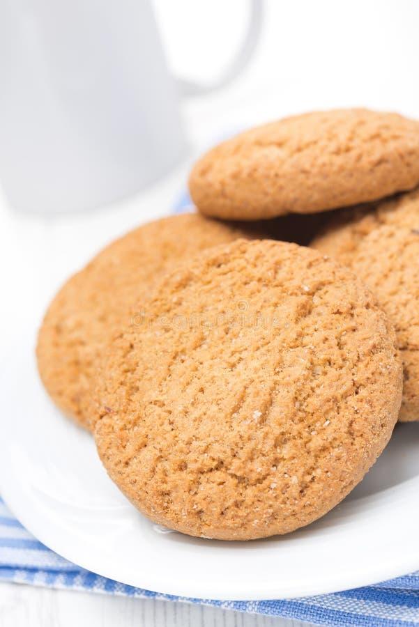 Biscotti di farina d'avena su un piatto e su una tazza di latte, primo piano immagini stock
