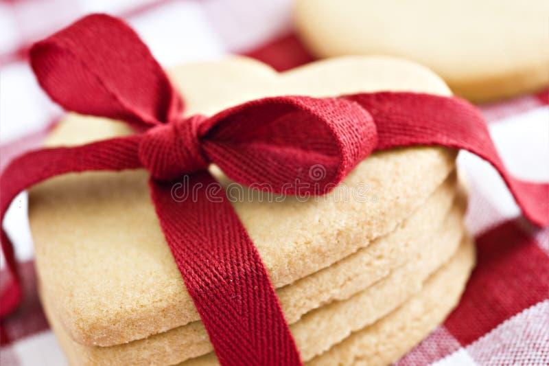Biscotti di figura del cuore con il nastro rosso fotografia stock