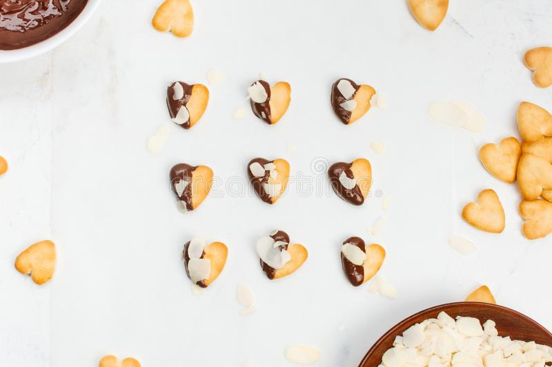 Biscotti di forma del cuore coperti di cioccolato e di mandorle su fondo di marmo fotografia stock