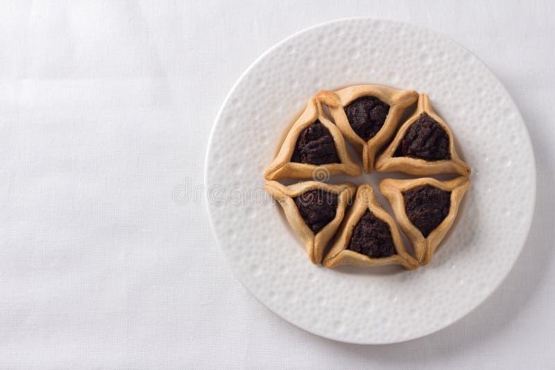 Biscotti di Hamantashen o orecchie di Aman, biscotti triangolari con i semi di papavero immagine stock libera da diritti