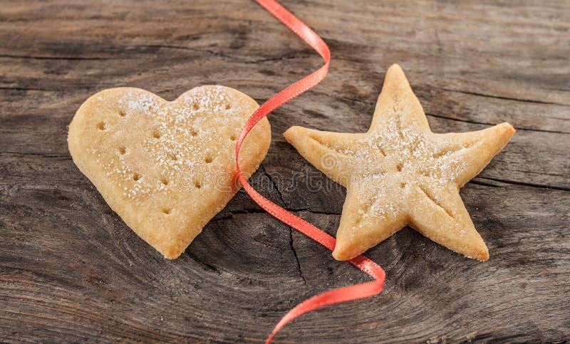 Biscotti di Natale e nastro rosso su fondo di legno d'annata fotografia stock