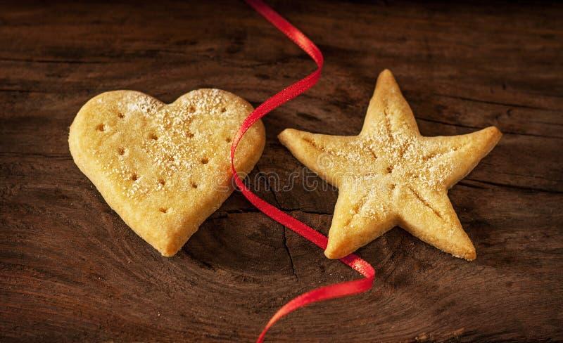 Biscotti di Natale e nastro rosso su fondo di legno d'annata immagine stock libera da diritti
