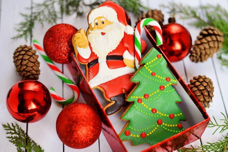 Biscotti di Natale ed alimento tradizionale del pan di zenzero sui rami dell'abete del bordo di legno fotografia stock libera da diritti