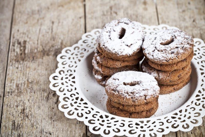 Biscotti di pepita di cioccolato al forno freschi con il mucchio della polvere dello zucchero sul fondo di legno rustico della ta fotografia stock libera da diritti