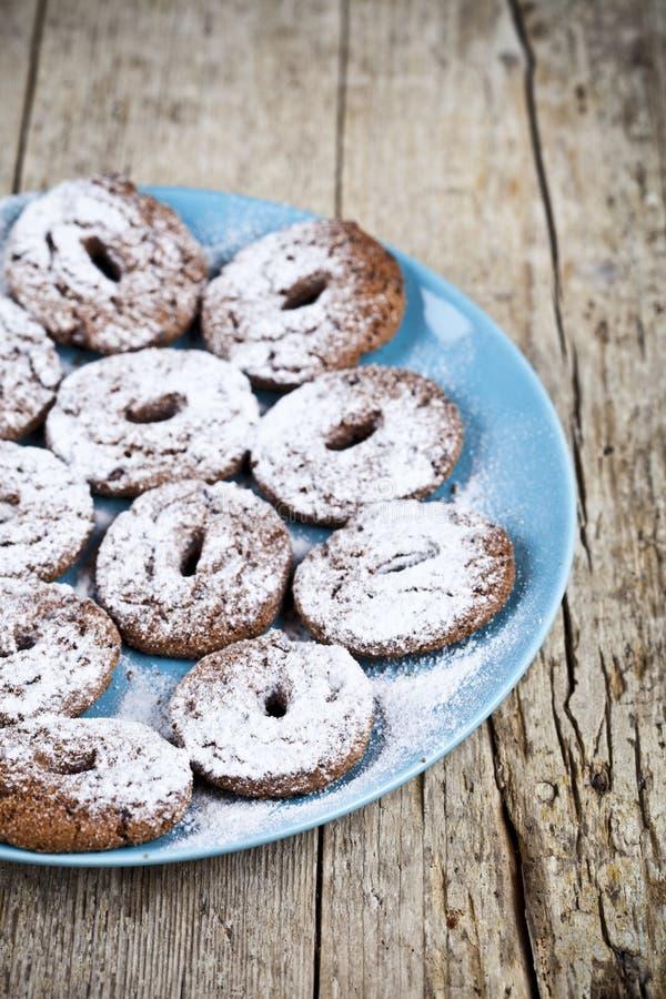 Biscotti di pepita di cioccolato al forno freschi con la polvere dello zucchero sul piatto blu sulla tavola di legno rustica fotografia stock libera da diritti