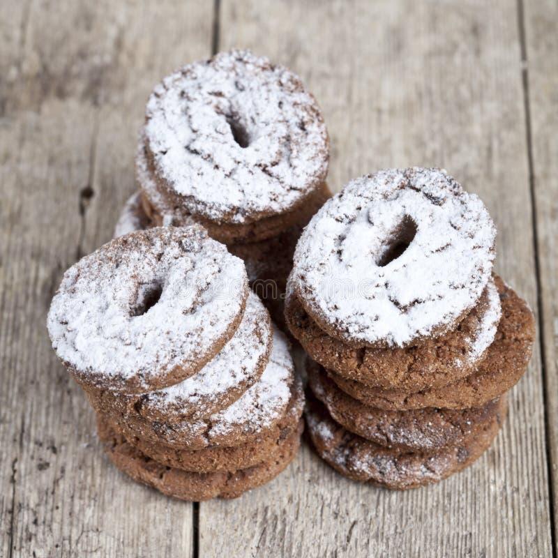 Biscotti di pepita di cioccolato al forno freschi con le pile della polvere dello zucchero sulla tavola di legno immagine stock libera da diritti