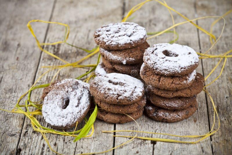 Biscotti di pepita di cioccolato al forno freschi con le pile della polvere dello zucchero sulla tavola di legno fotografie stock