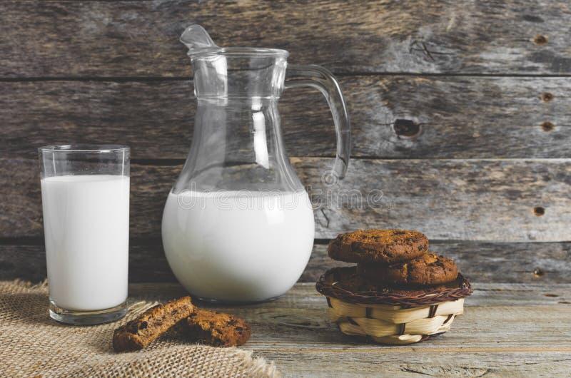 Biscotti di pepita di cioccolato della farina d'avena, brocca e bicchiere di latte, fondo di legno rustico immagine stock