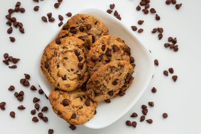 Biscotti di pepita di cioccolato innaffiati sul piatto bianco fotografia stock libera da diritti