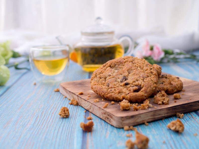 Biscotti di pepita di cioccolato saporiti impilati su un bordo servito con tè e la teiera sulla tavola di legno blu Spuntini casa immagine stock libera da diritti