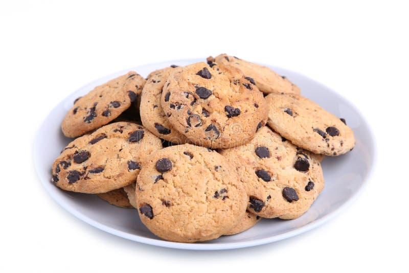 Biscotti di pepita di cioccolato sul piatto isolato su bianco immagini stock libere da diritti