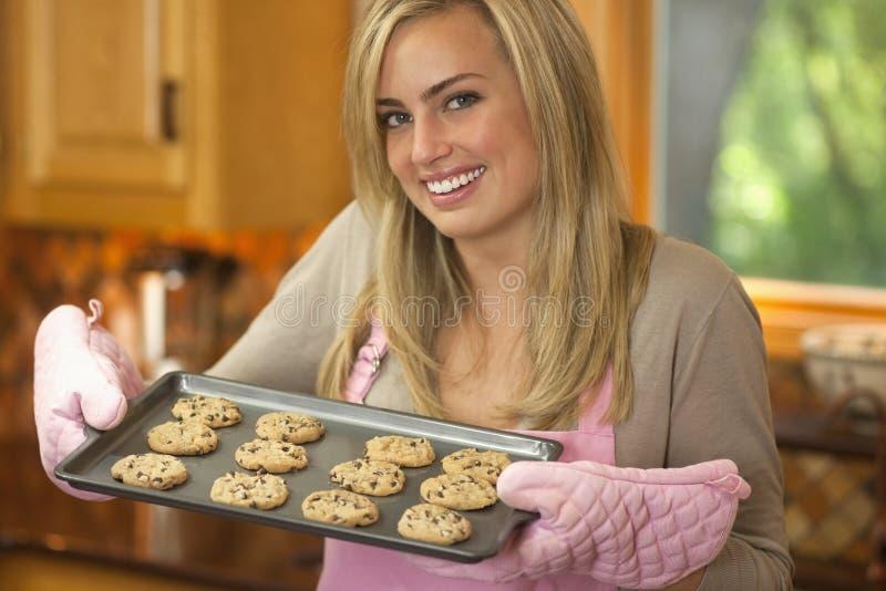 Biscotti di pepita di cioccolato di cottura della giovane donna fotografie stock libere da diritti