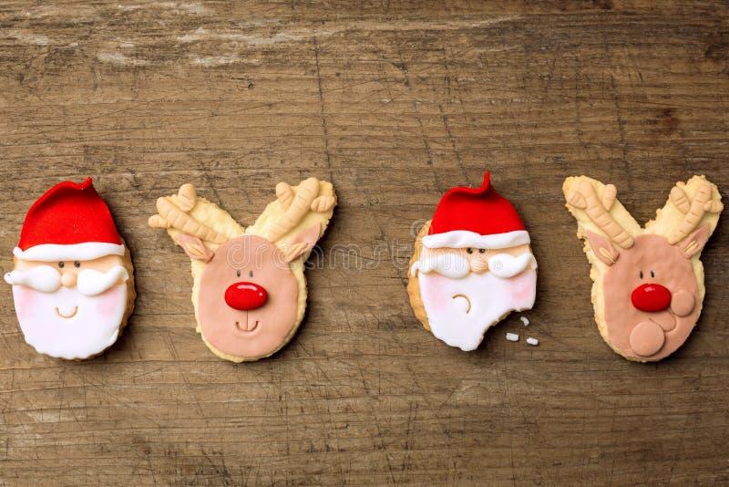 Biscotti divertenti Santa di natale e renna su fondo di legno fotografia stock libera da diritti