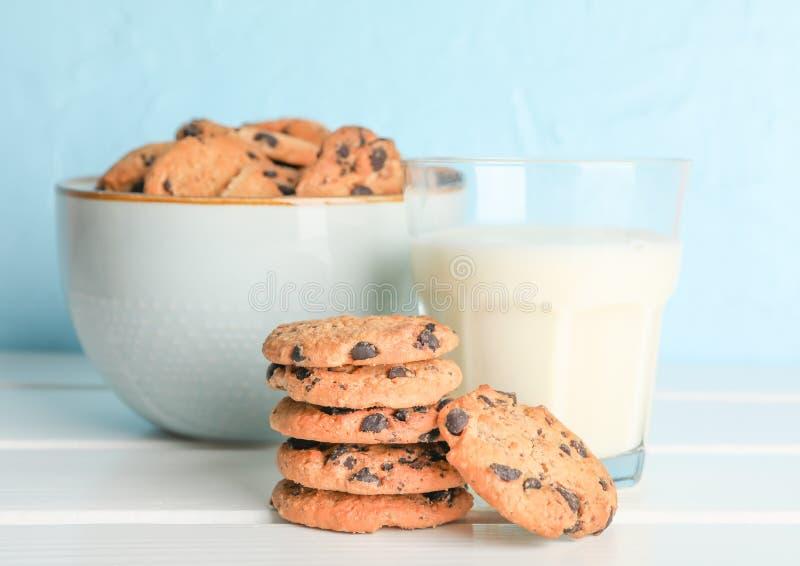 Biscotti e bicchiere di latte di pepita di cioccolato saporiti fotografia stock libera da diritti