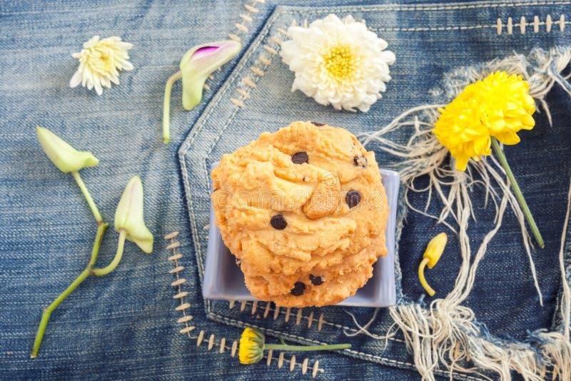 Biscotti e fiori di farina d'avena casalinghi sui jeans blu d'annata del denim immagine stock