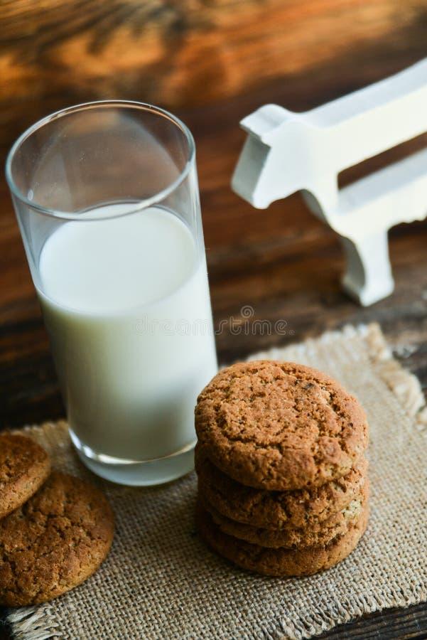 biscotti e latte di farina d'avena freschi su fondo di legno con le punte dell'avena immagini stock libere da diritti